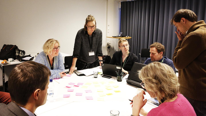 Osallistujia työskentelemässä pöydän ääressä Kuntien energiatehokkuus kannattavaksi -työpajassa.