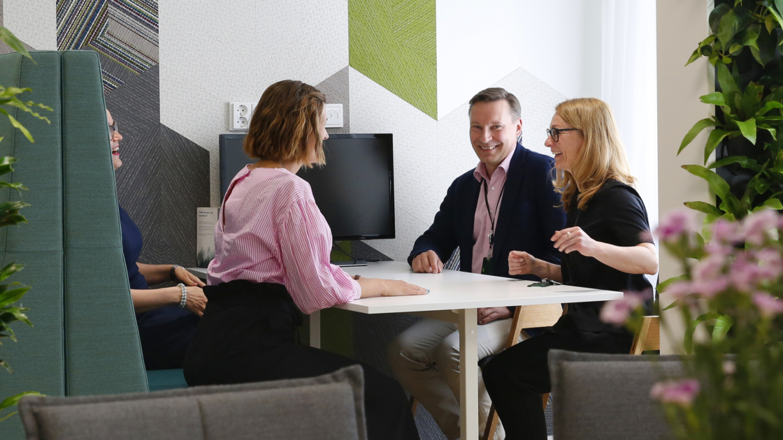 Kolme henkilöä istuu pöydän ääressä ja keskustelee SEB:in toimistolla.