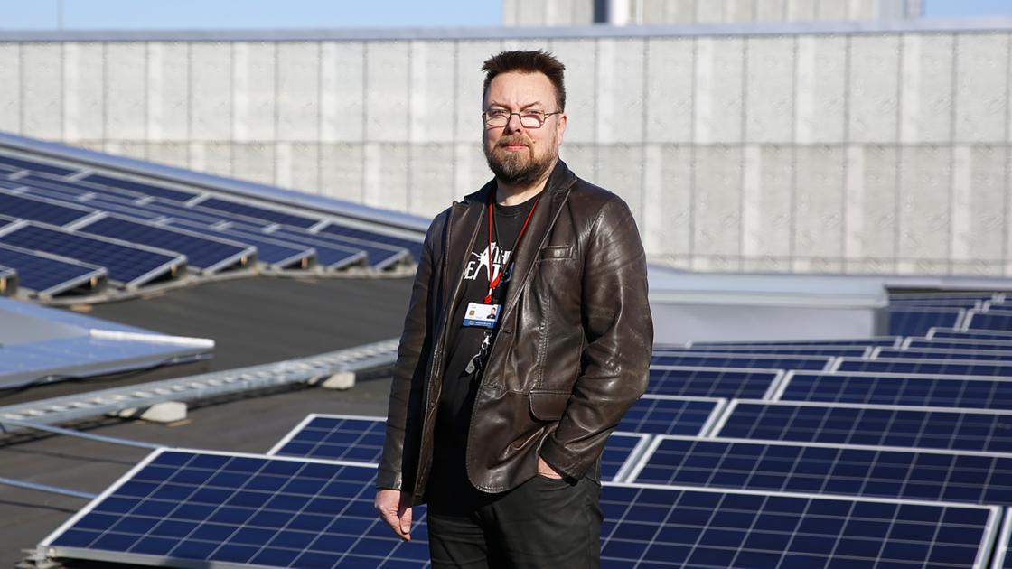 Ruokaviraston Ben Rydman seisoo katolla aurinkopaneeleiden edessä.