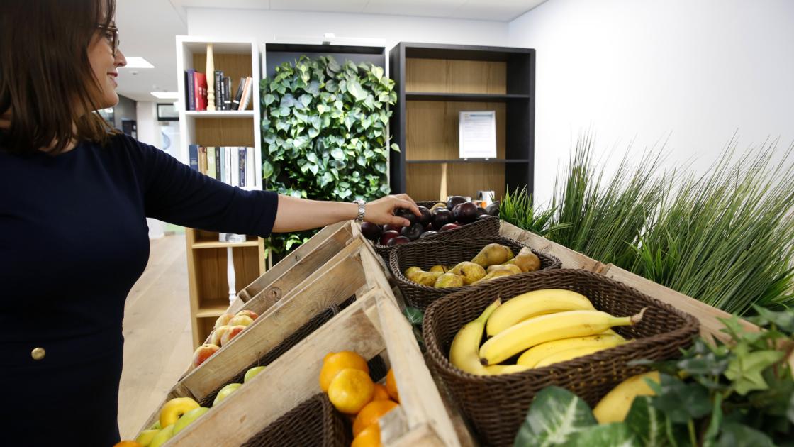 Hedelmiä tarjolla puulaatikoissa SEB:in toimistolla.. Hanna-Leena Holmberg kurottaa ottamaan hedelmää laatikosta.